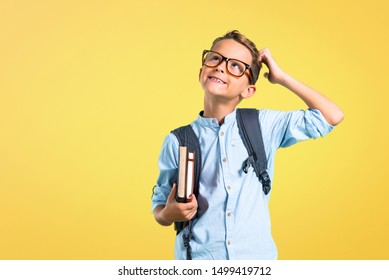 Student boy with backpack and glasses standing and thinking an idea on yellow background