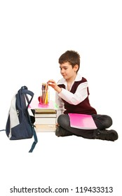 Student boy choice a pencil and prepare to make homework and sitting on the floor