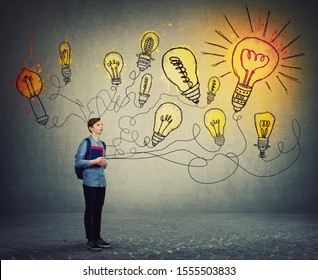 Student boy holding books and backpack imagining bright lightbulbs on the wall. Smart and ingenious teen guy has different thinking, genius creativity concept, alternative idea as the way to success.