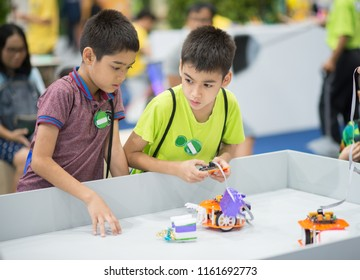 Student boys play and learn to control the robot in the class