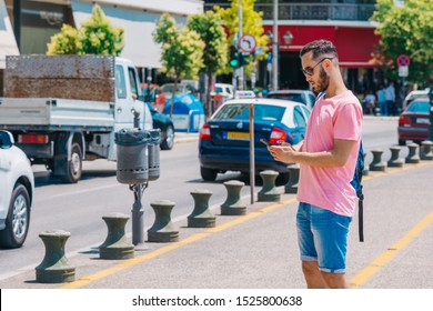 Student calling a taxi with his cell phone while wearing a backpack on his shoulder and standing on a city boardwalk. e-hailing concept