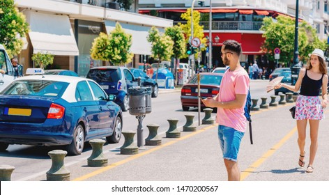Student calling a taxi while wearing a backpack on his shoulder and standing on a city boardwalk, e hailing concept