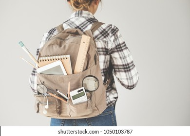 Student carrying backpack with stationery equipments