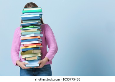 Student carrying stack of textbooks on color background. Studying process