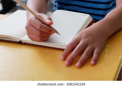 student child write on paper in class room