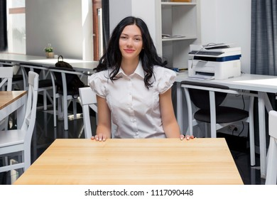 Student in classroom, happy, smiling girl sitting at desk. Girl at office, work place. Education, lesson, university, learning, work concept. Pretty, dark hair girl in white blouse, uniform