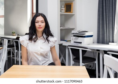 Student in classroom, happy, smiling girl sitting at desk. Girl at office, work place, indoors. Education, lesson, university, learning, work concept. Pretty dark hair girl in white blouse, uniform