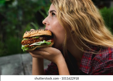 Student consume fast food. Girl bite of very big burger in the garden