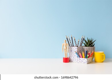 Student creative desk with colorful office supplies and blue wall background. Back to school.