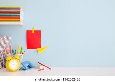Student-Kreativschreibtisch mit bunten Büroartikeln, Laptop und blauer Wand. Zurück zur Schule.