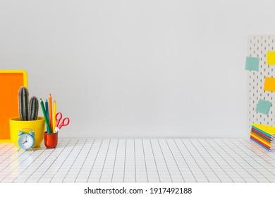 Student-Kreativschreibtisch mit bunten Büroartikeln, Laptop und weißer Wand. Zurück zur Schule.