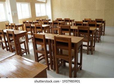 Student desks and chairs are arranged neatly in the classroom.