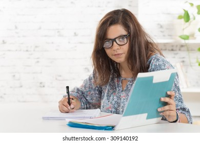 a student with eyeglasses working in her office