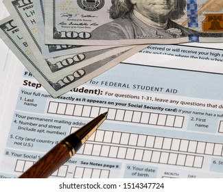 Student financial aid application forms for college tuition loans and grants with one hundred dollar bills and ballpoint pen