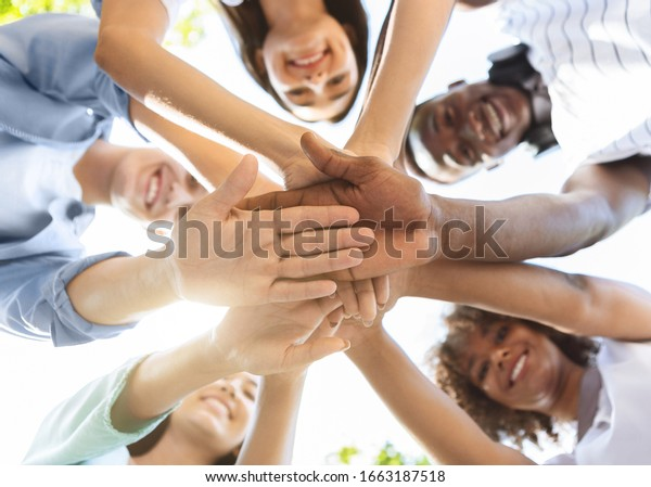 Student Friendship. Portrait of happy university friends stacking hands together, showing unity and togetherness, low angle view, selective focus