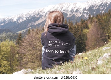 Student with a funny physics formula joke on her hoodie is enjoying freedom during a mountain hike