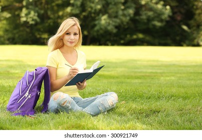 Student girl with book and backpack in park. Blonde young woman. Back to school