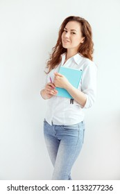 Student girl with book in hands near the white wall. Woman with long red curly hair. Office employee woman