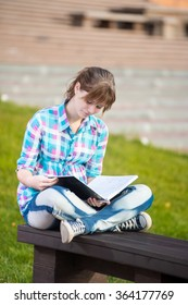 Student girl with copybook on bench. Summer campus park.