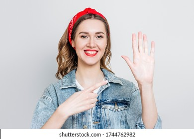 Student girl in denim jacket, bandana smiles and points to her left hand isolated on gray background, left-handed woman celebrating left-handed day