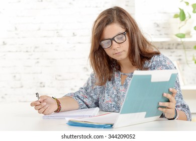 a student girl, with eyeglasses, does homework