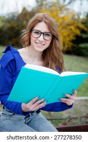 Student girl with glasses studying on campus