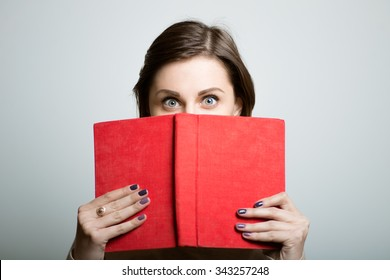 student girl hides behind the book. office manager. studio photo on a gray background
