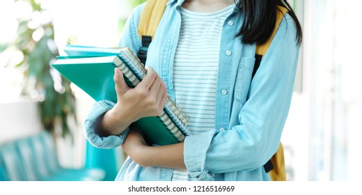 Student girl holding books and carry school bag while walking in school campus background, education, back to school concept