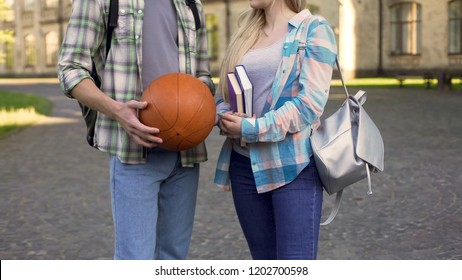 Student girl holding books and chatting with athletic man near college, flirt