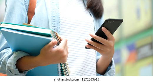 Student girl holding books and using smartphone, online education, technology communication