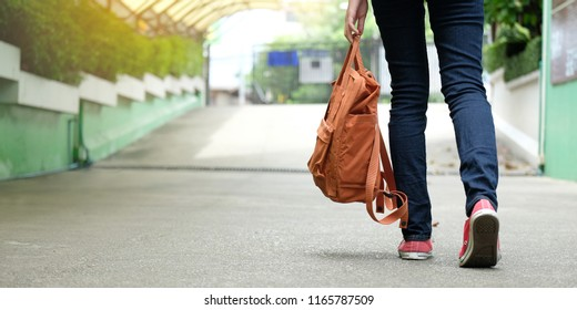 Student girl holding carry school bag while walking in school campus background, education, back to school concept