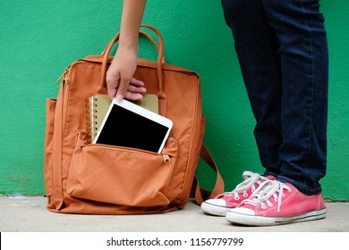 Student girl holding digital tablet from school bag, online education, adult learning concept