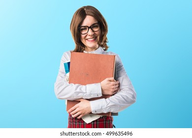 Student girl holding several college notes on blue backgound