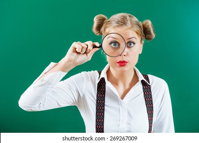 Student girl with loupe in front of blackboard