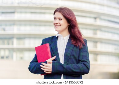 Student girl outdoor in campus smiling happy going back to University. Young student woman holding books and smiling over university building background.