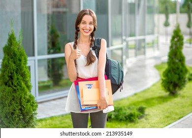 Student girl outdoors with backpack and books going to school and smiling