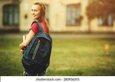 Student girl outside in summer park smiling happy. Caucasian college or university student. Young woman model wearing school bag outdoors in campus.