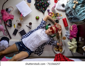 Student girl in a plaid shirt listening to music and thinking about the upcoming study at the University, lying on the floor. The mess in the ladies ' room, the image of the modern girl student
