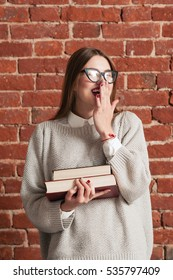 Student girl playfully laughing with books. Attractive woman covering her mouth with hand while enjoying funny joke. Coquette, flirt, fun, joy concept