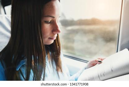 Student girl reading literature in train