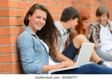 Student girl sitting with laptop outside campus friends in background