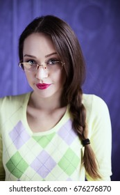 Student girl in studio wearing glasses and holding books