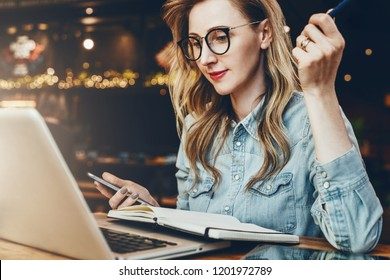 Student girl in trendy glasses sits in cafe in front of computer, laptop, watches an educational webinar. Businesswoman working remotely in coffee shop. Online education for adult, e-marketing.