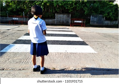 Student girl waiting to cross the crosswalk in front of school to return home after school. Can used for safety content.