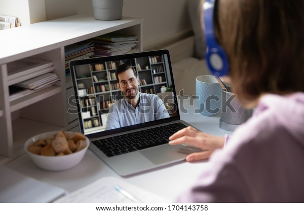 Student girl wearing headphones sitting at desk watching educational webinar, listen teacher during distant lesson via videoconference, view over woman shoulder laptop screen male tutor teach learner