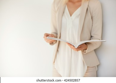 Student girl wearing white shirt and beige suit preparing for final exams at university. Attractive blonde female entrepreneur reading women's magazine while relaxing in cafe after working day