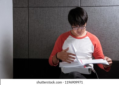 Student with glassed reading books for midterm exam, Young asian man learning by him self, Education concept