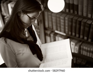 Student with glasses standing at bookshelf in old university library reading a book, sepia toned.
