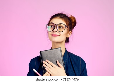 student in glasses thinks in hands calculator on pink background portrait