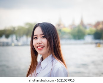 student and gradutation concept from portrait of asian beautiful girl(20s to 30s) with long black hair smile and happiness feeling with river background